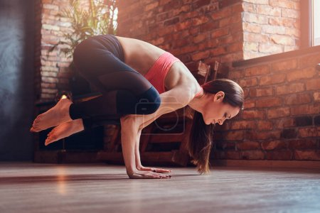 Middle-aged attractive woman balancing on hands and practicing yoga in a room with loft interior.