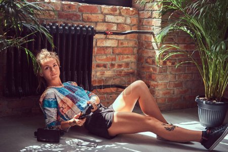 A beauty tattooed girl in casual clothes lies on the floor and plays video games in a room with loft interior against a brick wall.