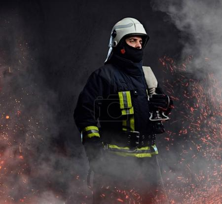 A professional firefighter in uniform holds the fire hose in fire sparks and smoke over a dark background.