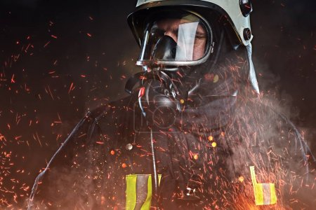 A professional firefighter dressed in uniform and an oxygen mask standing in fire sparks and smoke over a dark background.