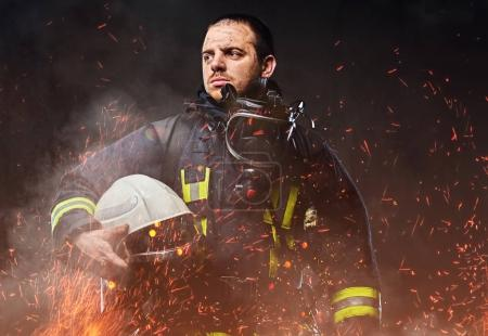 Photo for A professional firefighter dressed in uniform holding safety helmet in fire sparks and smoke over a dark background. - Royalty Free Image