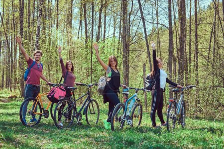 Active friends walk with bikes at forest in spring.