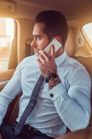 A handsome stylish businessman talking on the phone while sitting in the car.