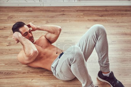 A handsome athletic male in sportswear doing exercise, lying on a wooden floor in the home.