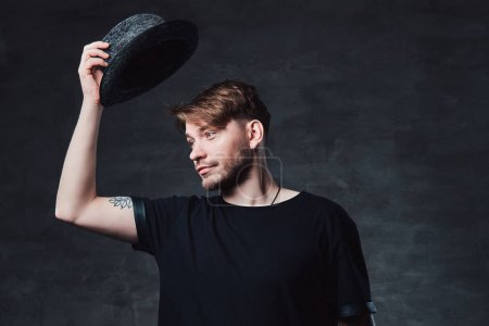 Studio portrait of a handsome fashionable male with tattooed arms, dressed in a black t-shirt holds a hat. Isolated on a dark background.