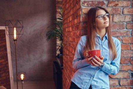 Photo pour Portrait d'une belle jeune femme avec une tasse de café appuyée contre un mur de briques dans une chambre au design loft . - image libre de droit