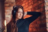 Close-up portrait a beautiful charming brunette in black sweater listens to music via good headphones while leaning against a brick wall in a room with loft interior.
