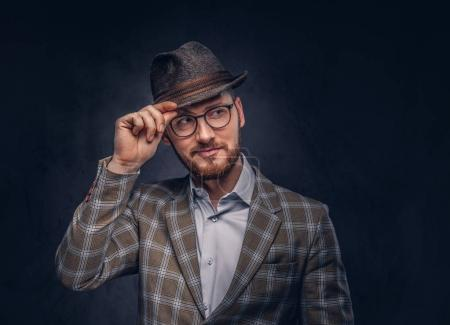 Studio portrait of a bearded hipster in hat and glasses wearing  casual suit.