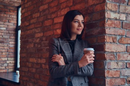 Portrait of a beauty businesswoman holds cup of a morning coffee