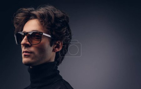 Studio portrait of a sensual macho male with stylish hair in a black sweater and sunglasses.
