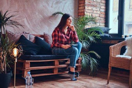 Photo pour Charmante brune dans une chemise en flanelle et un jean assis sur un canapé - image libre de droit