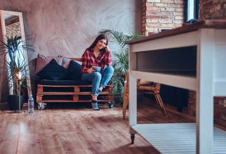 Photo pour Charmante brune dans une chemise en flanelle et un jean assis sur un sol - image libre de droit