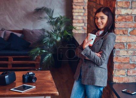 Photo pour Portrait d'une jeune photographe tenant une tasse de café du matin - image libre de droit