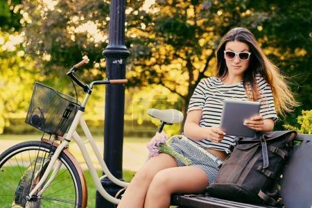 Photo pour Portrait d'une jolie brune assise sur un banc avec un vélo dans un parc municipal . - image libre de droit
