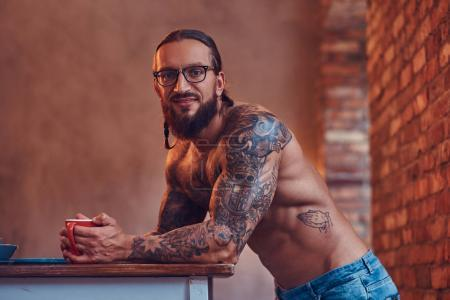 Handsome bearded tattooed male with a stylish haircut and muscular body, drinks coffee, leaning on a table.