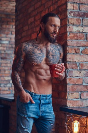 Photo pour Portrait d'un homme torse nu tatoué avec une coiffure et une barbe élégantes, boit du café du matin, appuyé contre un mur de briques dans une chambre . - image libre de droit
