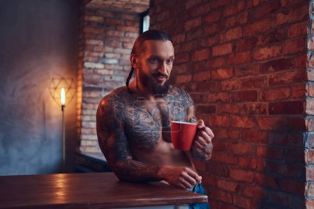 A handsome bearded tattoed male with a stylish haircut and muscular body, drinks coffee, leaning on a table.