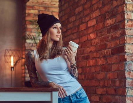 Photo pour Une femme blonde tatouée élégante en t-shirt et jeans - image libre de droit