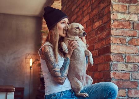 Photo pour Une femme blonde tatouée élégante en t-shirt et jeans avec ses chiens - image libre de droit