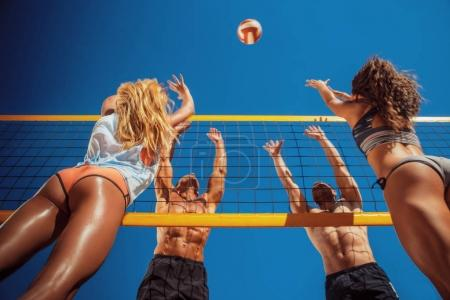 Young people playing volleyball on