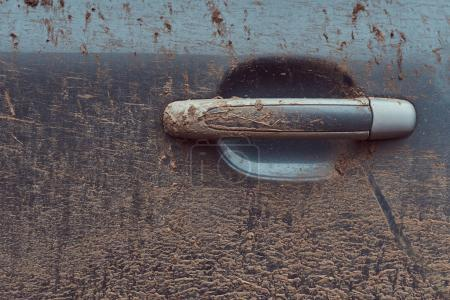 Close-up image of a dirty car after a trip around the countryside. Door handle.