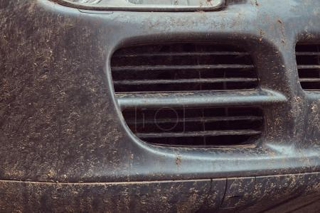 Close-up image of a dirty car after a trip off-road. Front view.