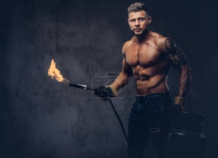 Brutal tattooed male welder with a stylish haircut and beard, with muscular body, dressed in only jeans, holds propane tank and a burning burner, standing in a studio, looking at a camera.  Isolated