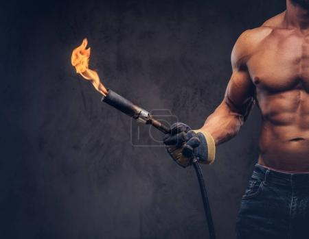 Cropped close-up image of a male welder with muscular body, dressed in only jeans, holds propane tank and a burning burner, standing in a studio.  Isolated on a dark background.