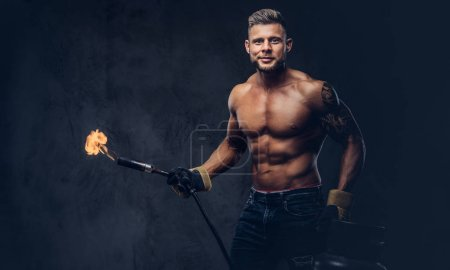 Brutal tattooed male welder with a stylish haircut and beard, with muscular body, dressed in only jeans, holds propane tank and a burning burner, standing in a studio, looking with a smirk. Isolated