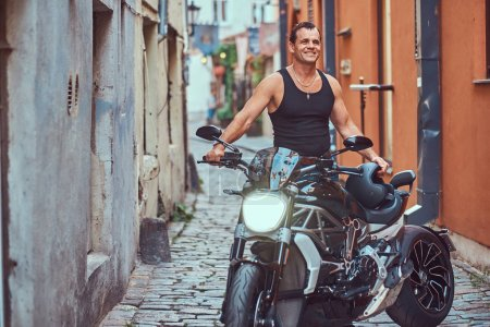 A handsome brutal biker dressed in a black t-shirt and jeans, with a charming smile, standing near a motorcycle, in a narrow old Europe street.