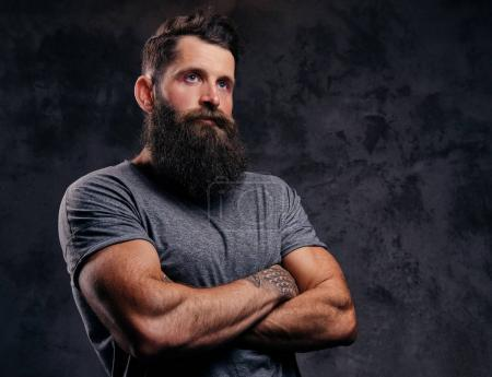 Photo for Close-up portrait of a hipster with full beard and stylish haircut, dressed in a gray t-shirt, stands with crossed arms in a studio on a dark background. - Royalty Free Image