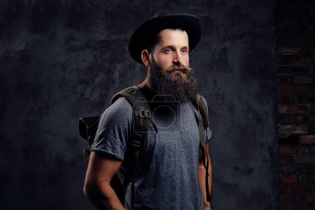 Photo for Close-up portrait of a handsome bearded traveler in hat with backpack. Isolated on a dark background. - Royalty Free Image