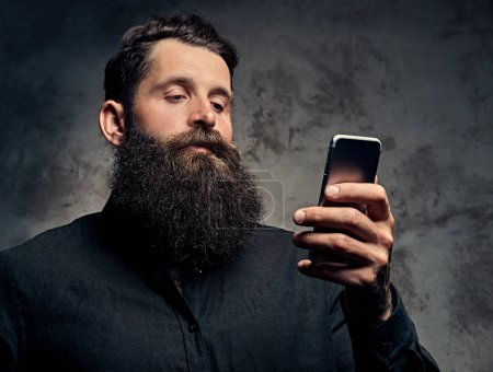 Photo for Portrait of a handsome bearded hipster dressed in a black shirt, using a smartphone, standing in a studio. Isolated on a dark background. - Royalty Free Image