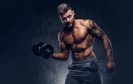 Powerful stylish bodybuilder with tattoo on his arm, doing the exercises on a biceps with dumbbell, look at the camera with a confident look. Isolated on a dark background.