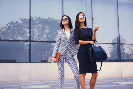 Portrait of two business women dressed in a stylish formal clothes, standing in a downtown against a background of skyscraper.