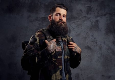 Photo for A handsome bearded traveler, dressed in a trendy camouflaged jacket, with a tattoed arms, standing in a studio. Isolated on a dark background. - Royalty Free Image