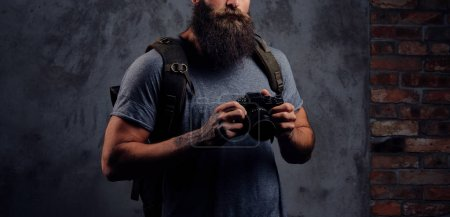 Photo for Portrait of a handsome bearded traveler in a hat with a backpack and tattooed arms, holds a photo camera. Isolated on a dark background. - Royalty Free Image