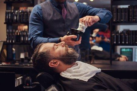 Master hairdresser prepares the face for shaving, deals foam.