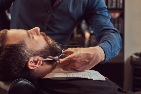 Professional hairdresser modeling beard with