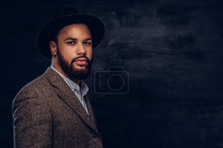 Photo for Studio portrait of handsome Afro-American male in an elegant brown jacket and hat. Isolated on a dark background. - Royalty Free Image