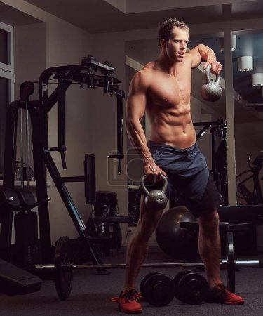 A handsome muscular shirtless bodybuilder man doing exercises on deltoid muscles with a kettlebell in the gym.