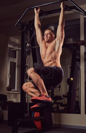 A muscular shirtless fitness man doing exercise on a horizontal bar to strengthen the abdominal muscles.
