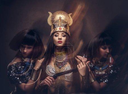 Photo pour Portrait de la reine égyptienne hautaine en costume de pharaon antique avec deux concubines. Isolé sur un fond sombre . - image libre de droit