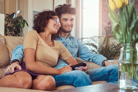 Young couple cuddling while watching TV at home.