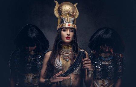 Photo pour Portrait de la reine égyptienne hautaine dans un costume antique Pharaon avec deux concubines. Isolé sur un fond sombre. - image libre de droit