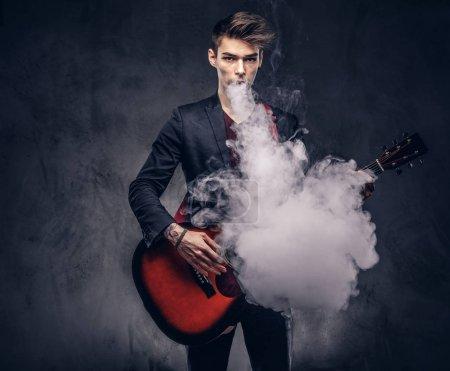 Photo pour Beau jeune musicien des cheveux élégants vêtements élégants exhale fumée tout en jouant de la guitare acoustique. Isolé sur un fond sombre. - image libre de droit
