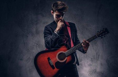 Photo pour Beau jeune musicien réfléchi des cheveux élégants vêtements élégants posant avec une guitare dans les mains. Isolé sur un fond sombre. - image libre de droit
