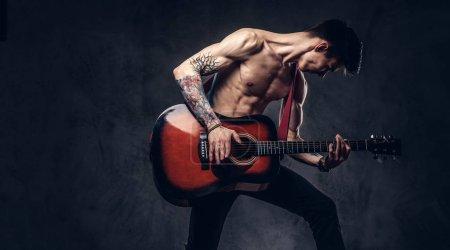 Photo pour Beau torse nu jeune musicien jouant de la guitare tout en sautant. Isolé sur un fond sombre. - image libre de droit