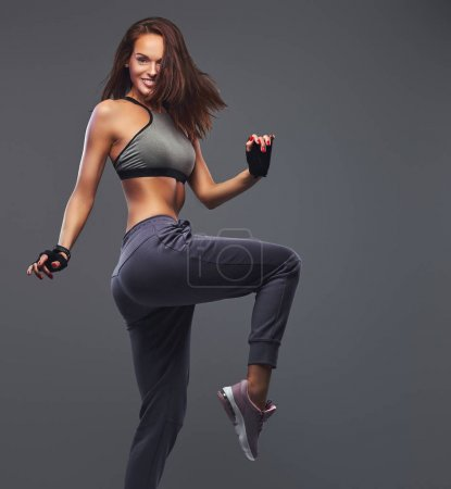 Photo for Smiling fitness brunette female in a gray sportswear posing in a studio. Isolated on a gray background. - Royalty Free Image