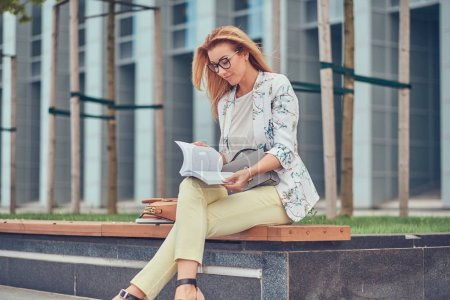 Charming blonde female in modern clothes, studying with a book, sitting on a bench in the park against a skyscraper.